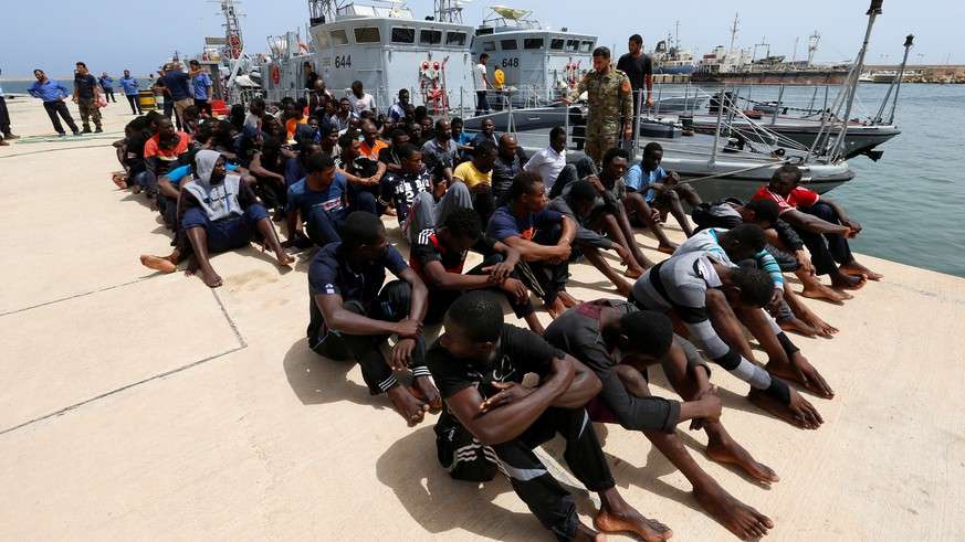 Migrants sit at a naval base after being rescued by Libyan coast guards in Tripoli, Libya July 3, 2018. REUTERS/Ismail Zitouny