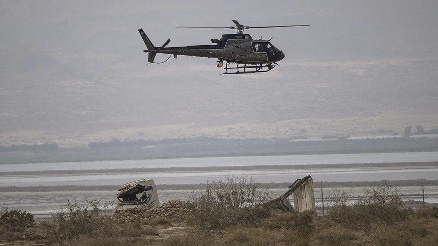 Israeli police helicopter searches the area above a truck that was swept in flood near Tzin river by the Dead Sea, Israel, Friday, April 27, 2018. Flash floods killed ten Israeli teenagers who were hiking south of the Dead Sea on Thursday, Israel's rescue service said. (AP Photo/Tsafrir Abayov)