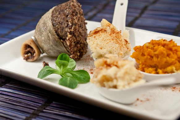 Haggis and turnip and potato mash and sweet potato mash presented in a plate with a cooked half haggis and a lamb's leaf lettuce, traditional food of Scotland presented in a modern way