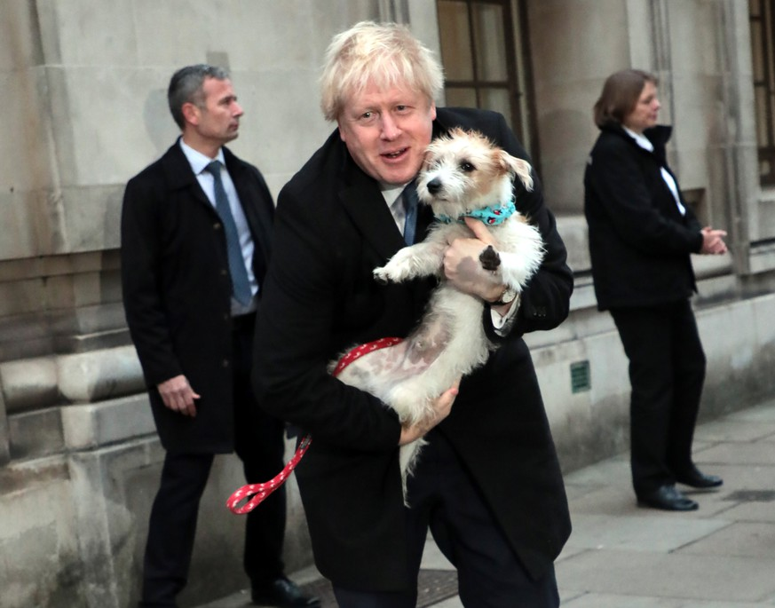 British Prime Minister Boris Johnson and his dog Dilyn leave a Westminster polling station after casting his vote on Thursday, December 12, 2019. Mr Johnson is seeking a majority in the General Election on December 12th to enable the government to get Brexit passed. PUBLICATIONxINxGERxSUIxAUTxHUNxONLY LON2019121212 HUGOxPHILPOTT