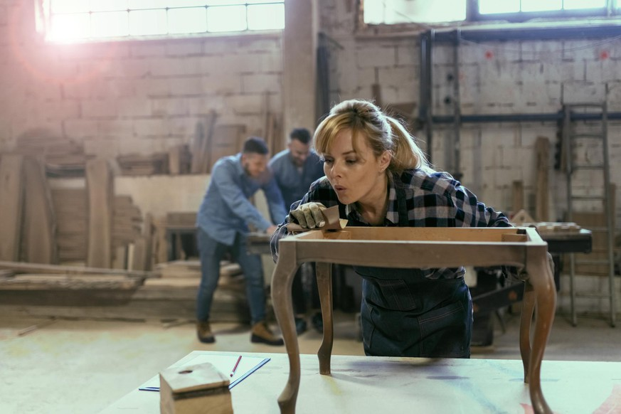 Portrait view of a female industrial worker in her 40s working as a carpenter in her workshop with sandpaper while her colleagues are in the background