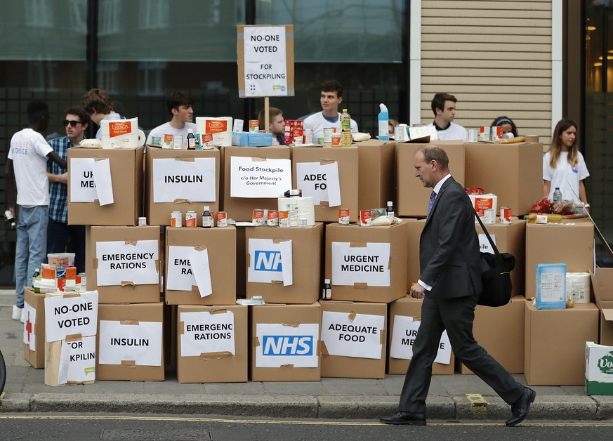 Anti Brexit activists protest as they deliver a pile of medical supplies in cardboard boxes to the Department of Health and Social Care in London, Wednesday, Aug. 22, 2018.  Our Future, Our Choice (OFOC) Pro EU campaign group wants get its message to the public surrounding the predicted costs of Britain's