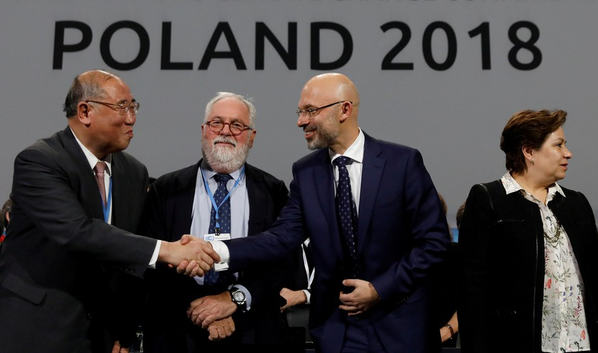 COP24 President Michal Kurtyka shakes hands with the head of Chinese delegation Xie Zhenhua, next to Miguel Canete, EU Comissioner and Executive Secretary of the UN Framework Convention on Climate Change Patricia Espinosa, after adopting the final agreement during a closing session of the COP24 U.N. Climate Change Conference 2018 in Katowice, Poland, December 15, 2018. REUTERS/Kacper Pempel     TPX IMAGES OF THE DAY