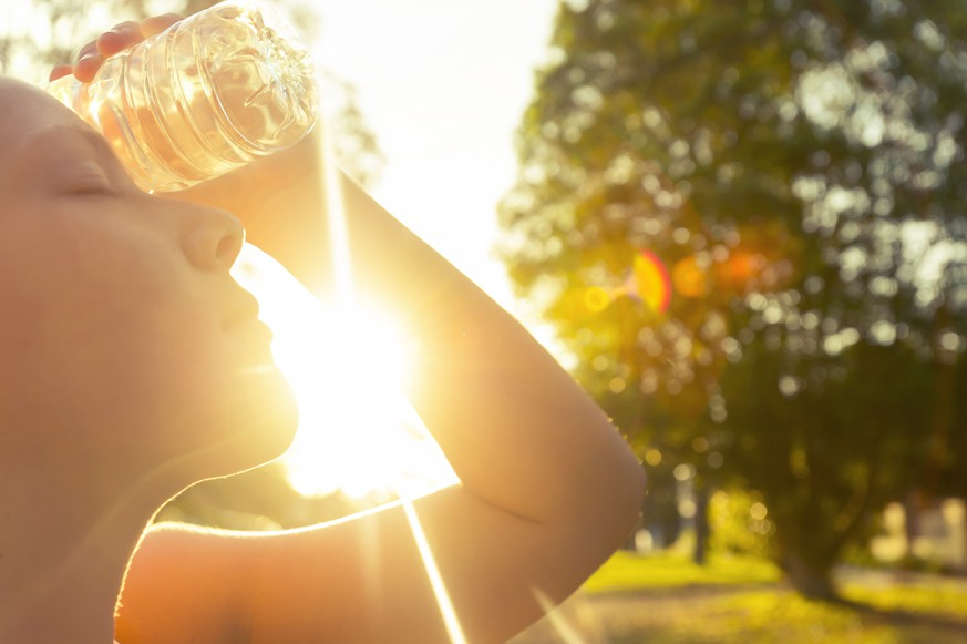 Woman using water bottle to cool down. Fitness and wellbeing concept with female athlete cooling down on a city street. She is holding a water bottle to her head to cool down. The sun is low creating long shadows and some lens flare. Copy space