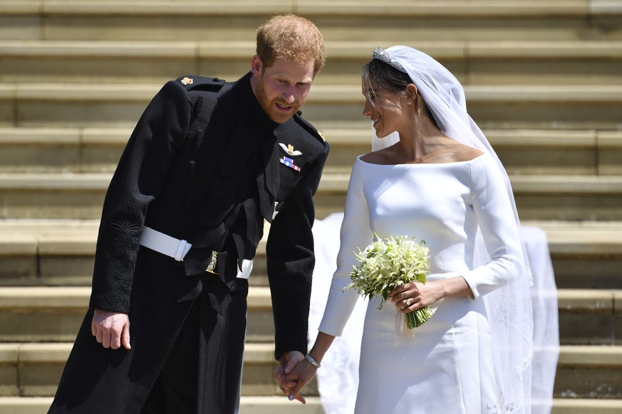 Britain's Prince Harry and his wife Meghan Markle walk down the west steps after their wedding ceremony at St. George's Chapel in Windsor Castle in Windsor, near London, England, Saturday, May 19, 2018. (Ben Stansall/pool photo via AP)