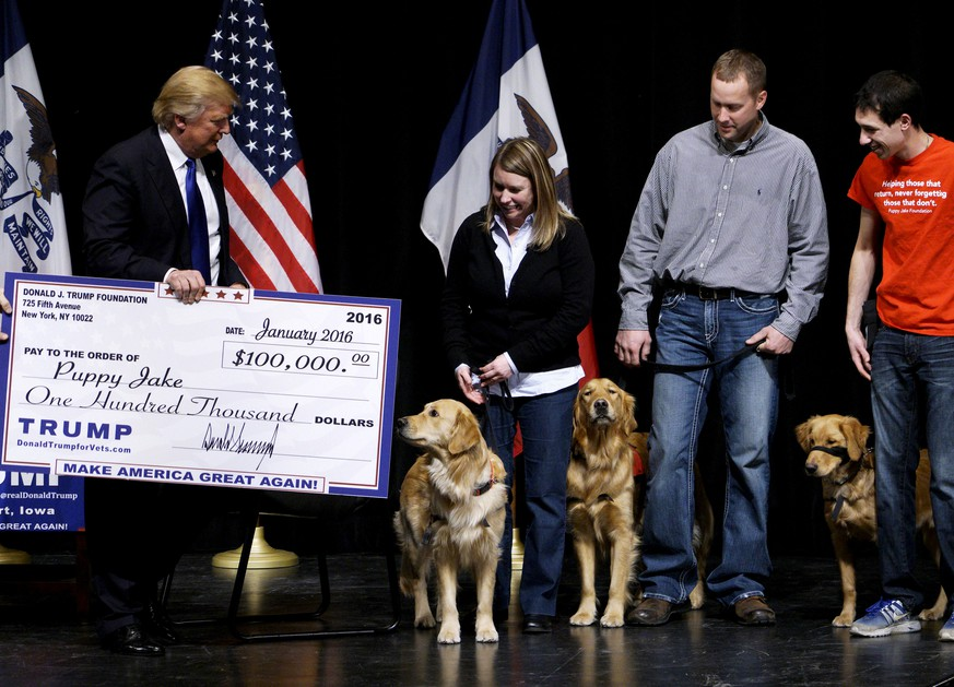 FILE PHOTO: U.S. Republican presidential candidate Donald Trump presents a mock check from the Trump Foundation representing $100,000 to members of the Puppy Jake Foundation, which provides military veterans with trained service dogs, in Davenport, Iowa, U.S., January 30, 2016.   REUTERS/Rick Wilking/File Photo