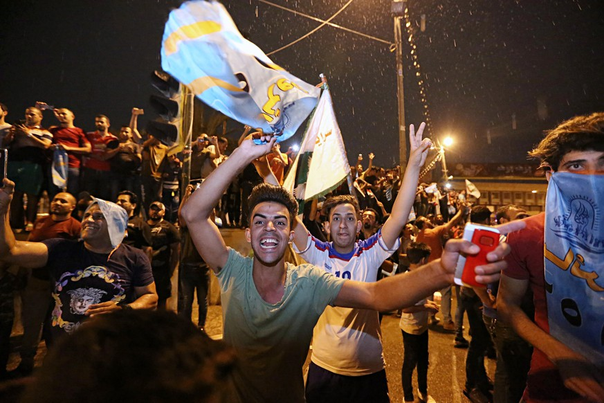 Followers of Shiite cleric Muqtada al-Sadr celebrate in Tahrir Square, Baghdad, Iraq, early Monday, May 14, 2018. Iraq's electoral commission announces influential Shiite cleric Muqtada al-Sadr is the current front-runner in national elections with official results in from just over half of the country's provinces. (AP Photo/Hadi Mizban)