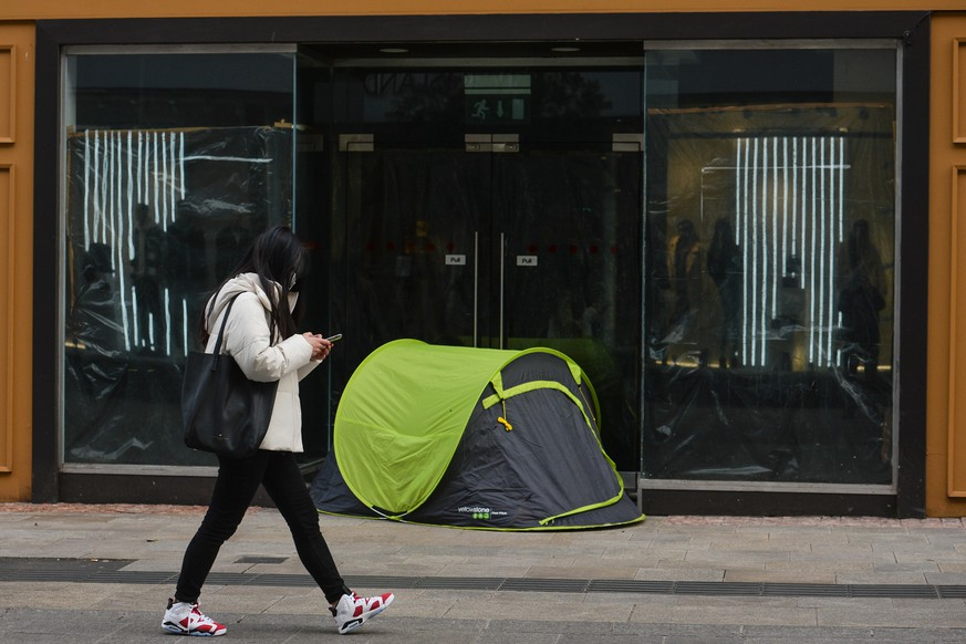 A young woman walks past a rough sleeper's tent on Grafton Street in Dublin city center during Level Five Covid-19 lockdown.  On Monday, March 1, 2021, in Dublin, Ireland. (Photo by Artur Widak/NurPhoto via Getty Images)