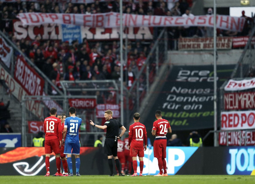 Referee Christian Dingert, center, talks to Hoffenheim and Munich players while Munich fans on the tribune display a banner reading