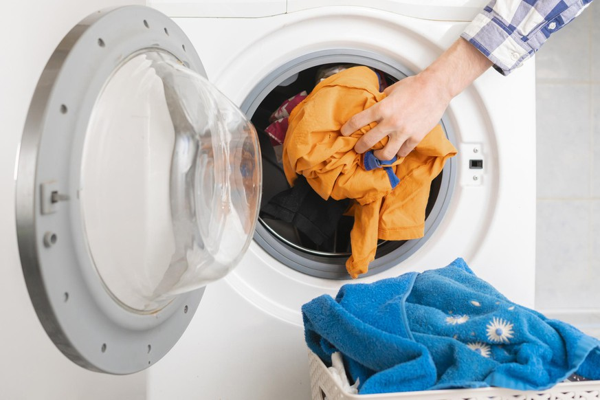 persons hand put dirty clothes in the washing machine