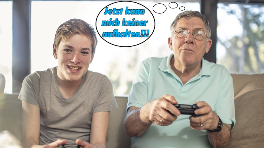 Grandfather and grandson playing video game on couch at home model released Symbolfoto property released PUBLICATIONxINxGERxSUIxAUTxHUNxONLY ZEF14779