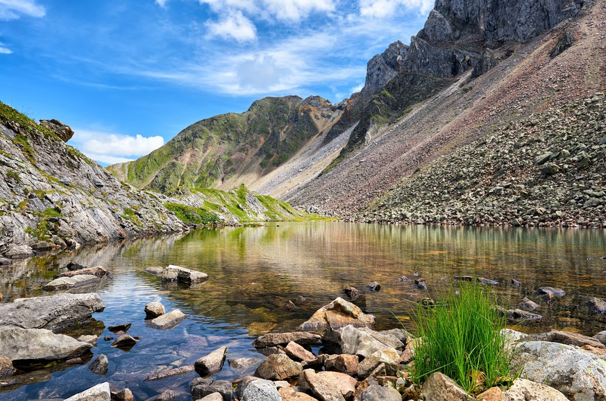 Little shallow lake with clear clear water in Siberian mountains. High mountain tundra. Eastern Siberia. Russia