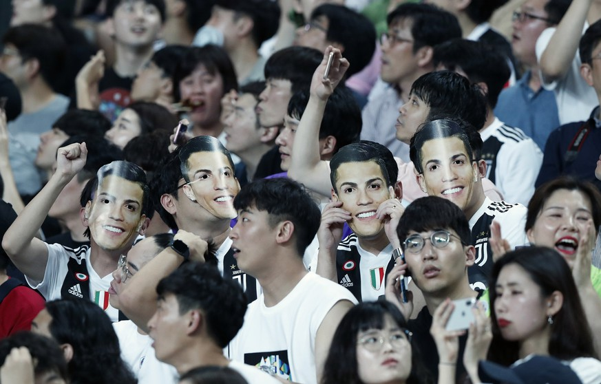 South Korean soccer fans wear masks of Cristiano Ronaldo of Juventus prior to a friendly match between Juventus and Team K League at the Seoul World Cup Stadium in Seoul, South Korea, Friday, July 26, 2019. (AP Photo/Ahn Young-joon)