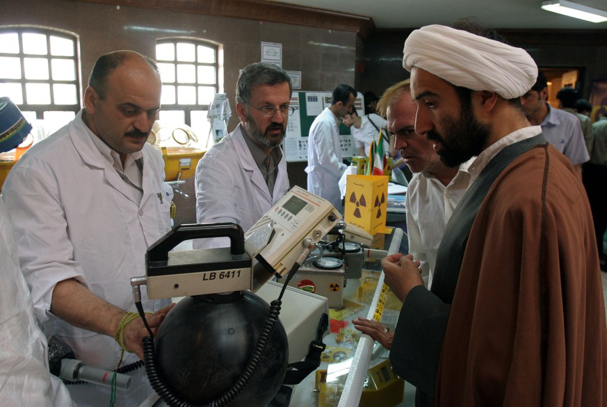 FILE - In this May 2, 2006 file photo, Iranian technicians explain a piece of equipment to a clergyman during an exhibition of Iran's Atomic Energy Organization at the Qom University in Qom, Iran. Iran's nuclear deal with world powers faces its biggest diplomatic challenge yet as President Donald Trump appears poised to withdraw the U.S. from the accord. (AP Photo/Vahid Salemi, File)