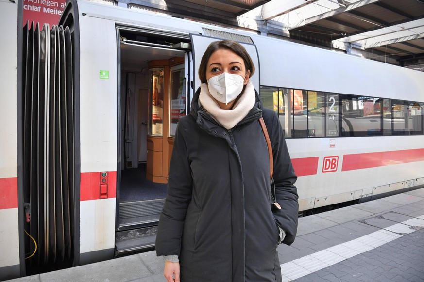 FOTOMONTAGE: Deutsche Bahn prueft Einfuehrung einer FFP2 Maskenpflicht. Junge Frau mit FFP2 Maske, Oeffentliches Leben in Zeiten der Coronavirus Pandemie. Geoeffnete Tuer an einem Waggon,Wagen von einem ICE Zug der DB am Hauptbahnhof. *** FOTOMONTAGE German Railways examines introduction of compulsory FFP2 mask Young woman with FFP2 mask, public life in times of coronavirus pandemic Opened door on a carriage, carriage of an ICE train of the DB at the main station