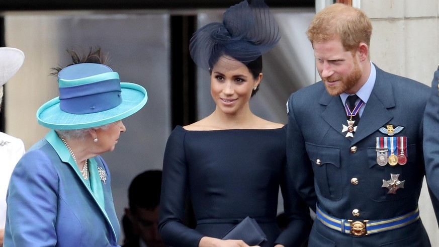 LONDON, ENGLAND - JULY 10:  (L-R)  Queen Elizabeth II, Meghan, Duchess of Sussex and Prince Harry, Duke of Sussex watch the RAF flypast on the balcony of Buckingham Palace, as members of the Royal Family attend events to mark the centenary of the RAF on July 10, 2018 in London, England.  (Photo by Chris Jackson/Chris Jackson/Getty Images)