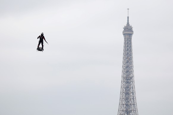 Franky Zapata flies on a Flyboard during the traditional Bastille Day military parade on the Champs-Elysees Avenue with the Eiffel Tower in the background in Paris, France, July 14, 2019. REUTERS/Charles Platiau     TPX IMAGES OF THE DAY