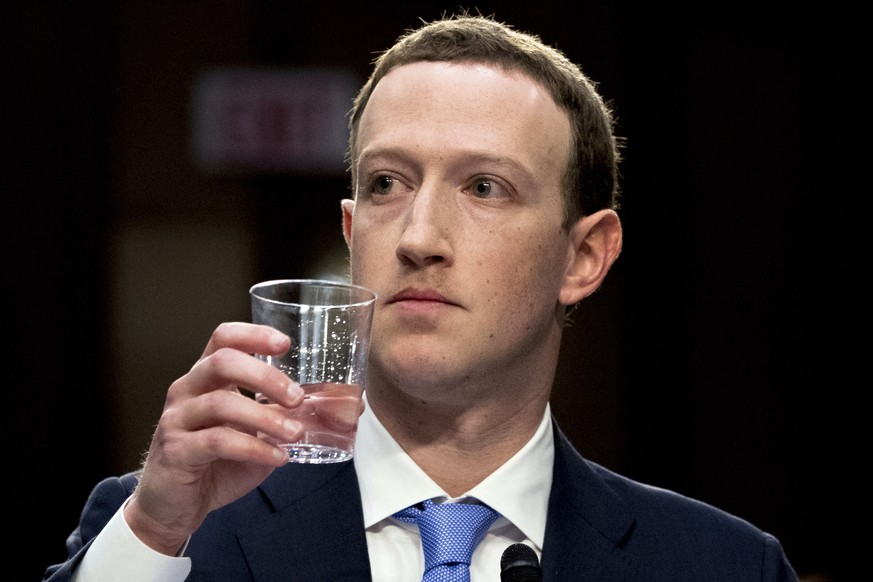 Facebook CEO Mark Zuckerberg takes a drink of water while testifying before a joint hearing of the Commerce and Judiciary Committees on Capitol Hill in Washington, Tuesday, April 10, 2018, about the use of Facebook data to target American voters in the 2016 election. (AP Photo/Andrew Harnik)