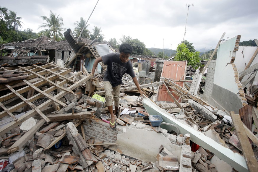 A man walks through debris from Sunday's earthquake in West Lombok, Indonesia, Saturday, Aug. 11, 2018. Scientist say the powerful Indonesia earthquake that killed more than 300 people lifted the island it struck by as much as 25 centimeters (10 inches). (AP Photo/Firdia Lisnawati)