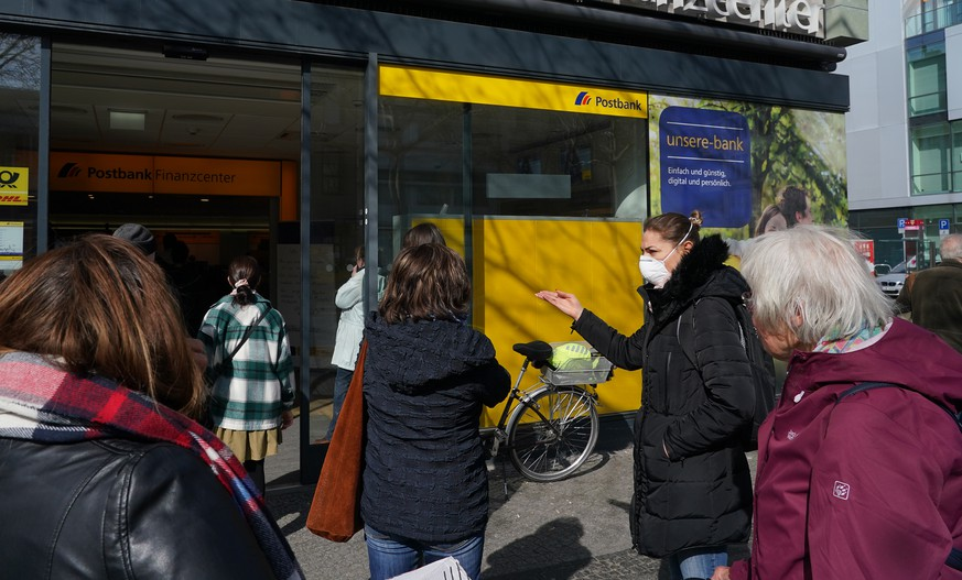 BERLIN, GERMANY - MARCH 18: People, including one woman wearing a protective face mask against the coronavirus, wait to enter a branch of bank Postbank on March 18 in Berlin, Germany. Everyday life in Germany has become fundamentally altered as authorities tighten measures to stem the spread of the coronavirus. Public venues such as bars, clubs, museums, cinemas, schools, daycare centers and non-essential shops have closed. Many businesses are resorting to home office work for their employees. And travel across the border to most neighboring countries is severely restricted.  (Photo by Sean Gallup/Getty Images)