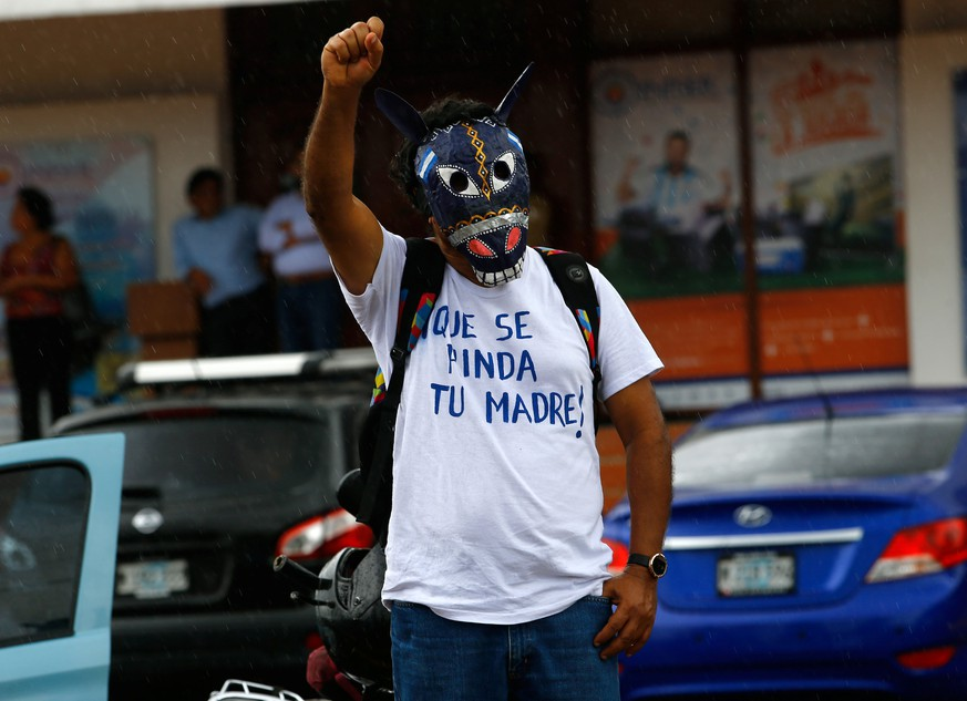 A demonstrator wearing a traditional mask takes part in a march called
