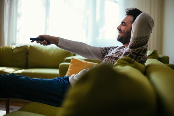 Man Using Remote Control In Front Of Television