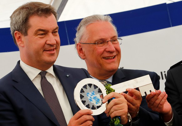 Markus Soeder, federal state premier of Bavaria (L) and Bavaria's interior minister Joachim Herrmann hold the symbolic key for Bavaria's new border police, burnishing the anti-immigration credentials amid a face-off with German Chancellor Angela Merkel in Passau, Germany July 2, 2018.  REUTERS/Wolfgang Rattay