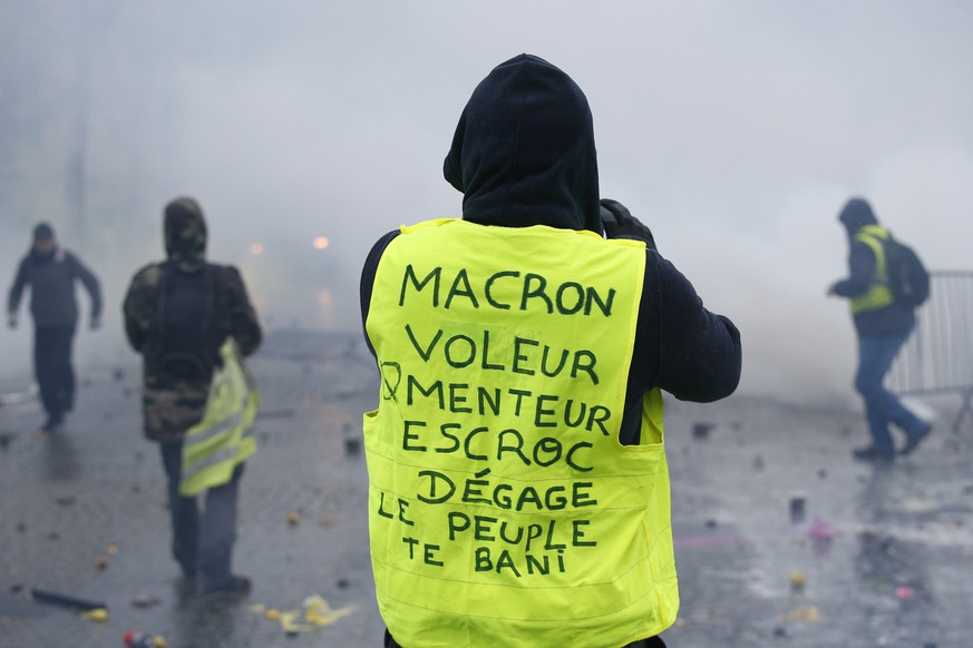 A demonstrator wearing a yellow jacket reading