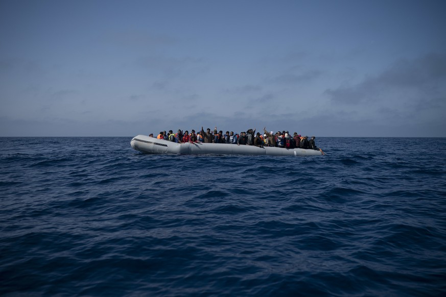 Refugees and migrants wait to be rescued by members of the Spanish NGO Proactiva Open Arms, after leaving Libya trying to reach European soil aboard an overcrowded rubber boat, north of Libyan coast, Sunday, May 6, 2018. In total 105 refugees and migrants from Bangladesh, Egypt, Nigeria, Marrocos, Gana, Pakistan, Sudan, Libya, Eritrea and Senegal were rescued in the overcrowded rubber boat. (AP Photo/Felipe Dana)