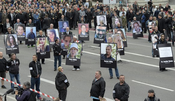 Demonstrators hold photos of people they claim have been killed by migrants during a demonstration in Chemnitz, eastern Germany, Saturday, Sept. 1, 2018, after several nationalist groups called for marches protesting the killing of a German man last week, allegedly by migrants from Syria and Iraq. (AP Photo/Jens Meyer)