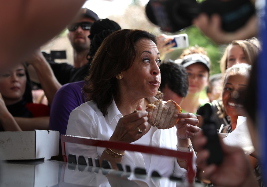 DES MOINES, IOWA - AUGUST 10: Democratic presidential candidate U.S. Sen. Kamala Harris (D-CA) eats a pork chop on a stick while attending the Iowa State Fair on August 10, 2019 in Des Moines, Iowa. Kamala Harris is on a five day river-to-river bus tour across Iowa promoting her