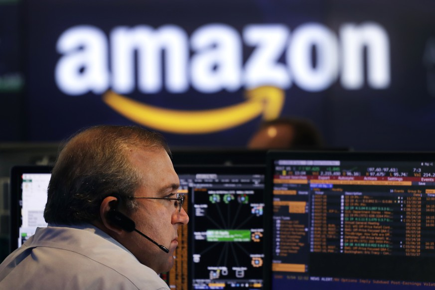 A Nasdaq employee monitors market activity Tuesday, Sept. 4, 2018, in New York. Amazon became the second publicly traded company to be worth $1 trillion, hot on the heels of Apple. (AP Photo/Mark Lennihan)