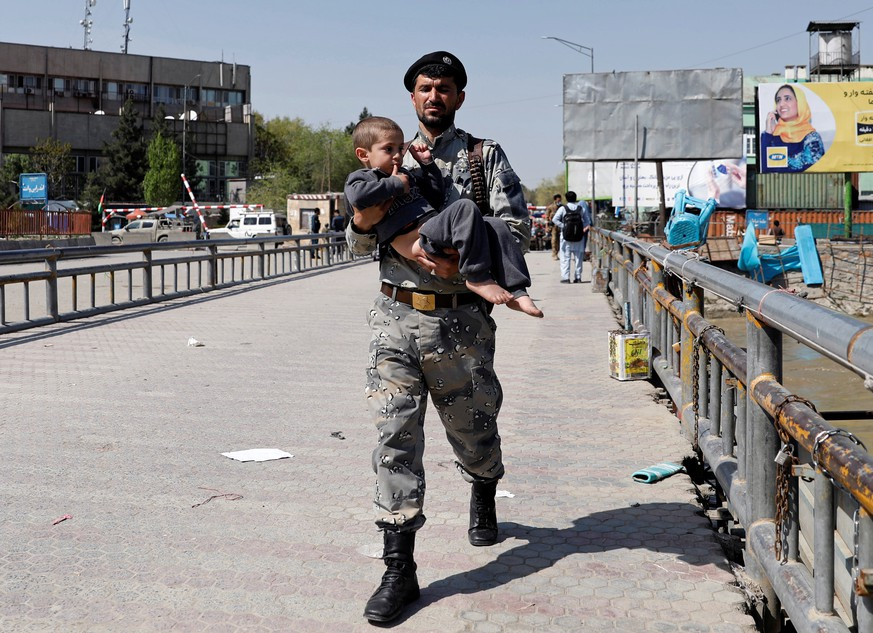 An Afghan security force officer carries a child rescued from the building of Ministry of Communication and Information Technology in Kabul, Afghanistan April 20, 2019. REUTERS/Mohammad Ismail