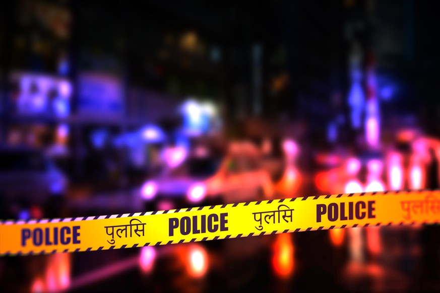 A night time street scene with focus on safety Police tape in Hindi. Hindi is spoke in Uttar Pradesh, Haryana, Himachal Pradesh and the capital Delhi in North India; Bihar and Jharkhand in Eastern India; Madhya Pradesh and Chhattisgarh in Central India and Rajasthan in West India.