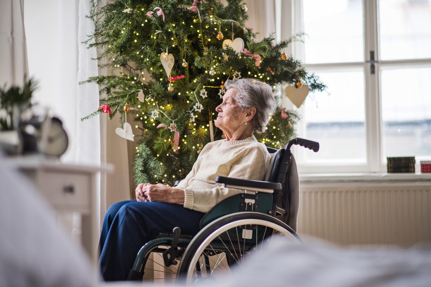 A lonely senior woman in wheelchair at home at Christmas time, looking out of a window.
