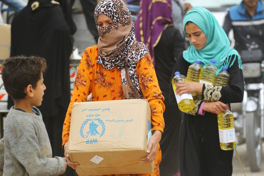 FILE PHOTO: Women carry food aid given by UN's World Food Programme in Raqqa, Syria April 26, 2018. REUTERS/Aboud Hamam/File Photo