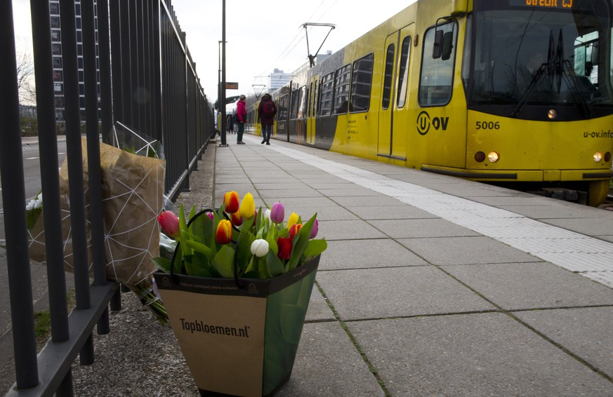 A tram passes flowers at the site of a shooting incident in a tram in Utrecht, Netherlands, Tuesday, March 19, 2019. A gunman killed three people and wounded others on a tram in the central Dutch city of Utrecht Monday March 18, 2019. (AP Photo/Peter Dejong)