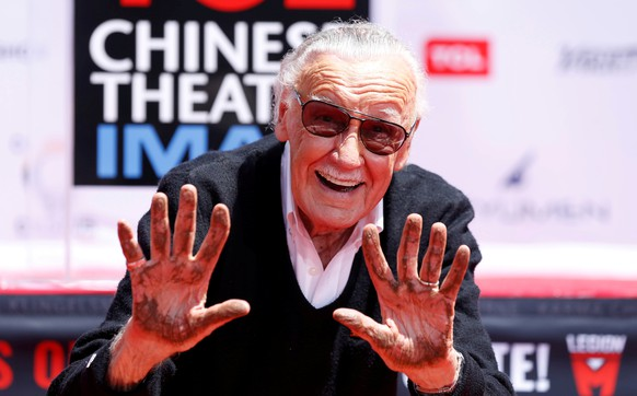 Marvel Comics co-creator Stan Lee shows his hands after placing them in cement during a ceremony in the forecourt of the TCL Chinese theatre in Los Angeles, California, U.S., July 18, 2017.   REUTERS/Mario Anzuoni