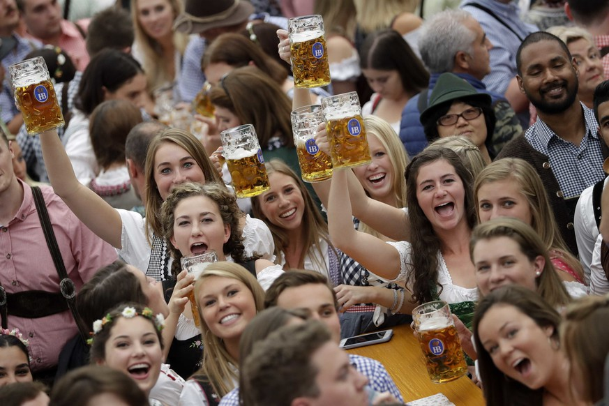 Young people celebrate the opening of the 185th 'Oktoberfest' beer festival in Munich, Germany, Saturday, Sept. 22, 2018. The world's largest beer festival will be held from Sept. 22 until Oct. 7, 2018. (AP Photo/Matthias Schrader)