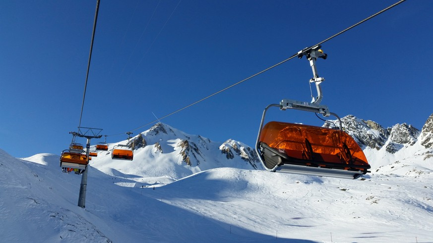a high capacity chairlift taking skiers up the snow covered mountains and ski field of Ischgl, Austria.