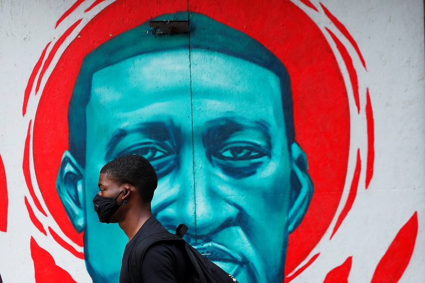 A man wearing a protective mask walks past a mural of George Floyd, in the aftermath of his death in Minneapolis police custody,  in Chicago, Illinois, U.S., July 27, 2020.  REUTERS/Shannon Stapleton