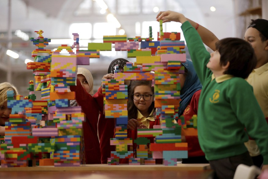 Children from the local Globe Primary School help build a Lego sculpture during a photocall to promote the exhibition