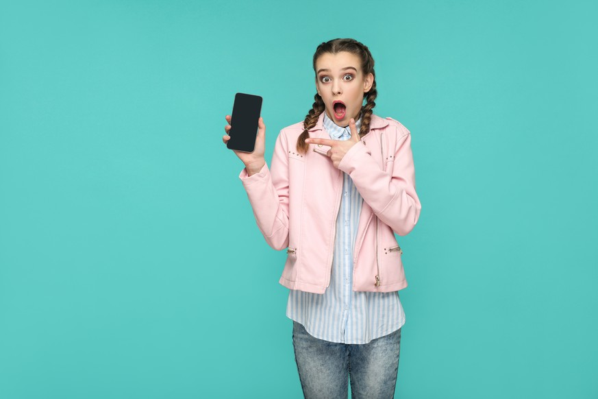 shocked funny girl in casual or hipster style, pigtail hairstyle, standing, holding and pointing at mobile display, screen with surprised face, Indoor studio shot, isolated on blue or green background