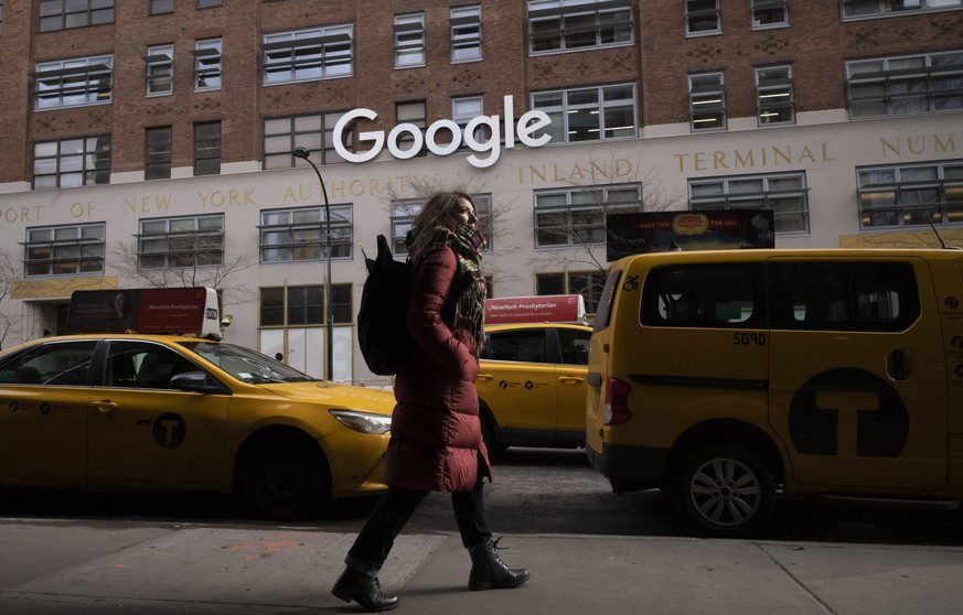FILE- In this Dec. 17, 2018, file photo a woman walks past Google offices in New York. Russian news reports say that Google has agreed with national authorities to delete links to websites banned in Russia. The daily Vedomosti reported Thursday, Feb. 7, 2019, that Google has reached an agreement with the Russian state media oversight agency, Roskomnadzor, to regularly receive updated lists of banned sites and delete links to them upon review. The newspaper says Google has already removed about 70 percent of the banned websites from its search results.  (AP Photo/Mark Lennihan, File)