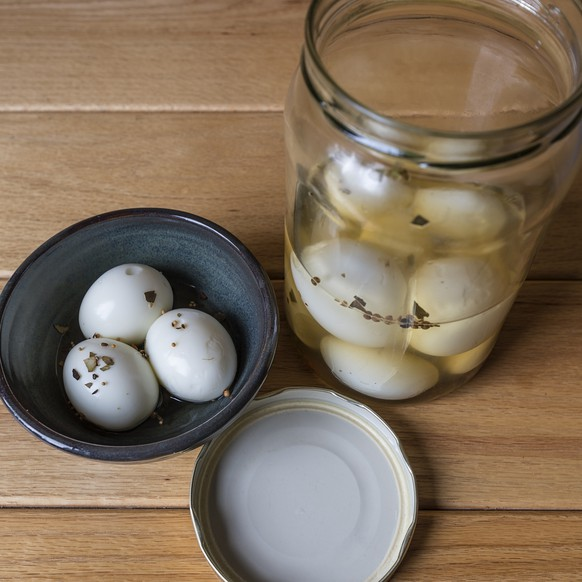a bowl and jar of pickled eggs