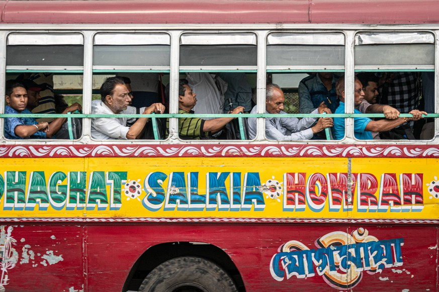 May 23, 2019 - Kolkata, West Bengal, India - Indian men sit on a colorful public bus on the Howrah Bridge in the Bara Bazar, Barabazar Market district, in Kolkata formerly Calcutta, in West Bengal, India, on 23 May 2019. Kolkata India PUBLICATIONxINxGERxSUIxAUTxONLY - ZUMAn230 20190523_zaa_n230_1548 Copyright: xDiegoxCupolox
