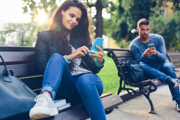 Teenage couple using smartphones in the city park
