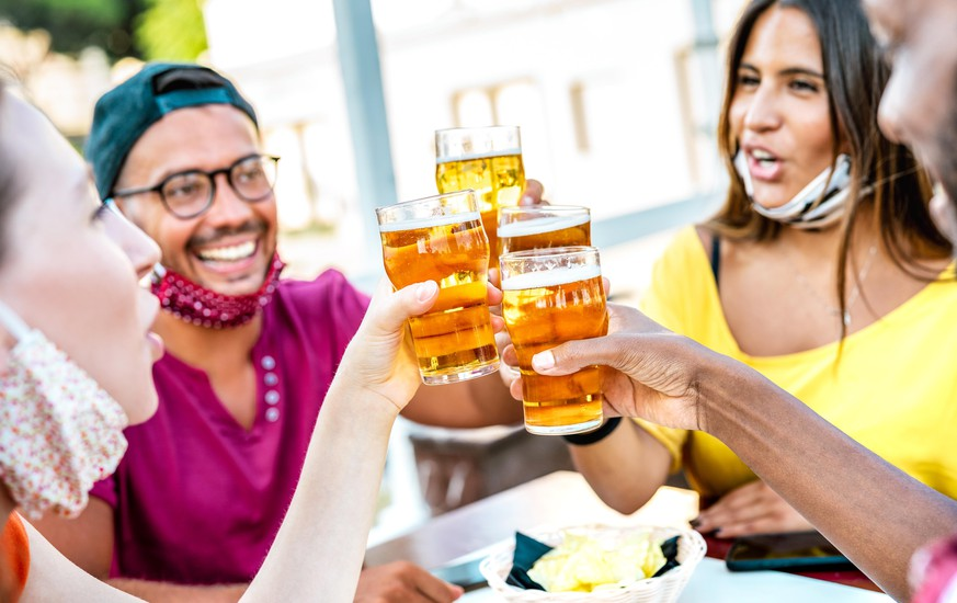 Friends toasting beer glasses with opened face masks - New normal lifestyle concept with people having fun together drinking on happy hour at brewery bar - Bright warm filter with focus on brew pints
