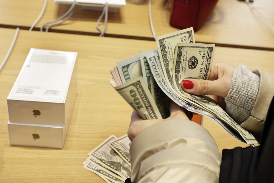 FILE- In this Nov. 3, 2017, file photo, a customer counts out cash for the purchase of two iPhone X's at the Apple Store on New York's Fifth Avenue. The Trump administration's hit list of Chinese products facing import taxes includes key components used in gadgets that can be wirelessly operated through a smartphone or another device. The tariffs also will nail networking equipment that makes the internet work. Trump has also threatened to impose tariffs on a total of $500 billion worth of Chinese items. That could affect major technology products such as Apple's iPhones, which are assembled in China. (AP Photo/Richard Drew, File)