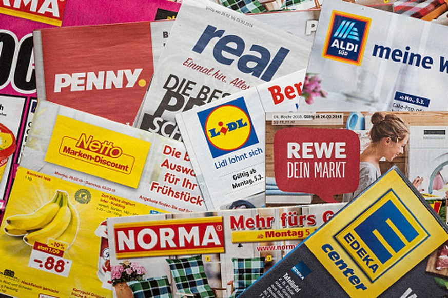 Amberg, Germany - February 26, 2018: Advertising leaflets of some German supermarket chains. Logos and brands are visible. Lidl, Aldi Süd, Penny Markt, Norma, Netto, Edeka, Real, Rewe.